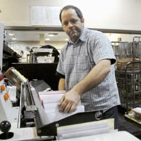 Postal worker Mike Boles sorts letters in the processing plant of the Carbondale, Ill., Post Office in this 2010 AP file photo.