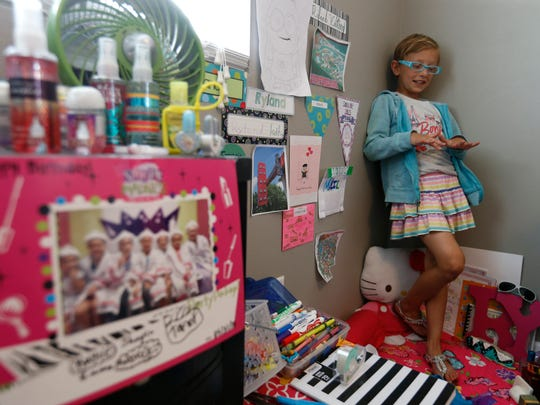 Ryland Kelting, 9, stands in his favorite corner of his room Saturday, May 28, 2016, as he talks about a previous party (pictured at left) when he and his friends got their nails done.