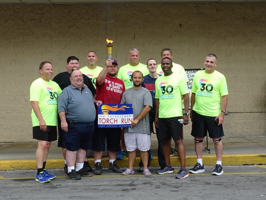Law enforcement officers who carried the Special Olympics torch through Bucyrus on Thursday take a moment to chat with students from the city's Fairway School, an institution that educates those with special needs.