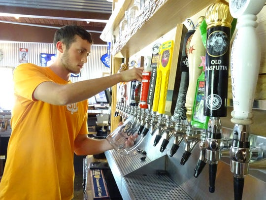 Austin Smith pours one of the 25 craft beers on tap