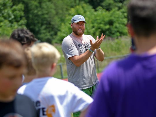 Green Bay Packers tight end Justin Perillo, a Tatnall School graduate, shows kids in a football camp at Tatnall proper form for catching a football.