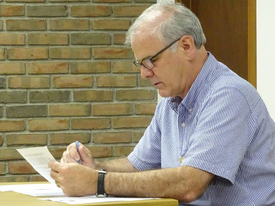 Mayor Jeff Reser looks over notes Wednesday during the city's traffic commission meeting. It was decided that traffic signals downtown should be timed to help pedestrians safely cross the streets.