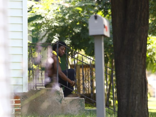 A man sits under a shady doorsteps Tuesday afternoon in Wausau.