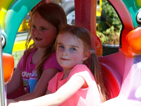 Emma Wallace, 6, left, and her 4-year-old sister Anna, both of Merrill, riding a ride Friday at the Lincoln County Fair in Merrill.