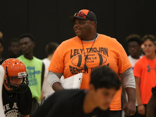 New Lely football head coach Maurice Belser looks on as players do stretches in the gym during the first day of fall football practice on Monday, August 1, 2016.