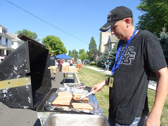 Jeremy Claypool of Bucyrus grills hot dogs for city