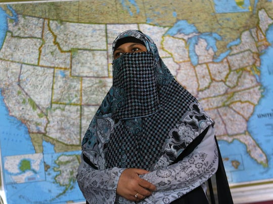 Anna Latif, director of the Tarbiyah School in Newark, sits in a classroom with the map of the United State behind her.