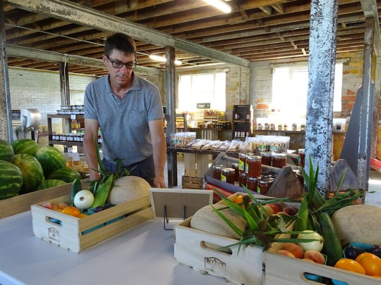 Kent Stuckey, owner of Pickwick Place in Bucyrus, sets down a crate of vegetables Friday in the venue's market. The facility is featured in the latest edition of Our Ohio, a magazine printed by the Ohio Farm Bureau.