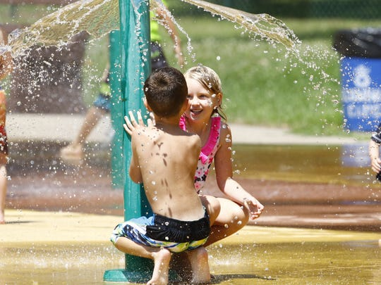Two kids duck under an umbrella water at the Marathon Park Splash Pad in Wausau.
