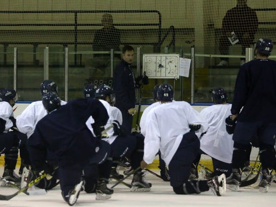 Everblades players gather around head coach Brad Ralph during Tuesday morning's training camp at Germain Arena.