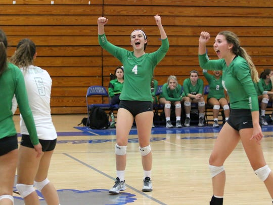 Sarah Davis, center, and the Fort Myers volleyball team celebrate a point during Thursday night's Class 7A regional semifinals at Barron Collier.