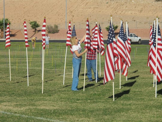 Linda Stieber helps set up flags Sunday morning for