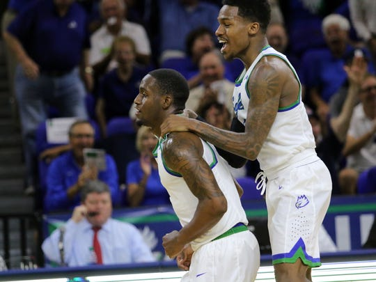 Brandon Goodwin, right, celebrates Zach Johnson's 70-foot halftime buzzer-beater during Wednesday night's game against Binghamton.