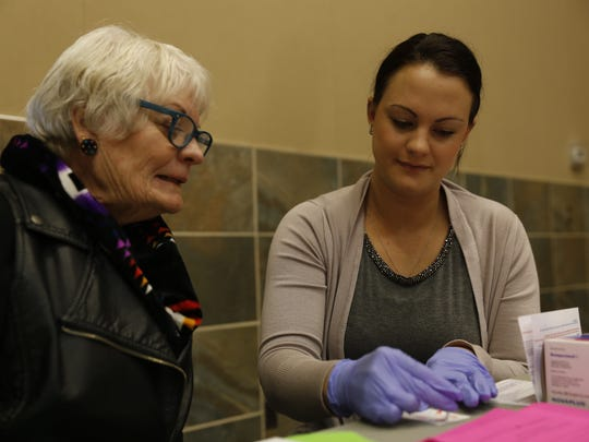 Kristan Velarde, a donor recruiter for United Blood Services, right, uses a sample of blood from Jane Banes, right, to find out Banes' blood type during the health fair Saturday at the Farmington Civic Center.
