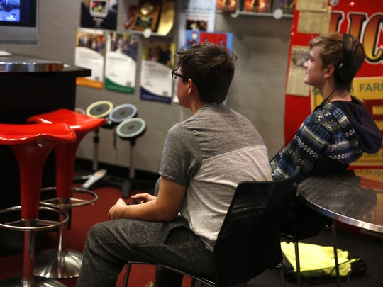 Orion Dees, left, and William Knight concentrate on their video game Saturday at the Farmington Public Library. The library's daily gaming sessions are one of its biggest attractions for young people.