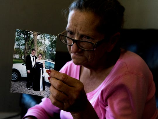 Lorie Foltz reads the notes on the back of a photograph of her daughter Cody Goodrich and a date dressed for prom on Wednesday, February 15, 2017. Foltz said she had been going through pictures of Goodrich recently. Goodrich was shot in the head by an abusive boyfriend in January 2016, when she tried to end the relationship. She survived. Foltz has not left her side since.