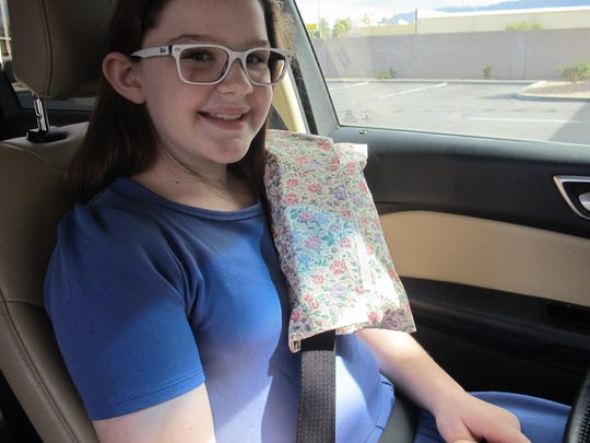 Shaynie Abbott shows the proper way to fasten the portacath pillow to the seatbelt.
