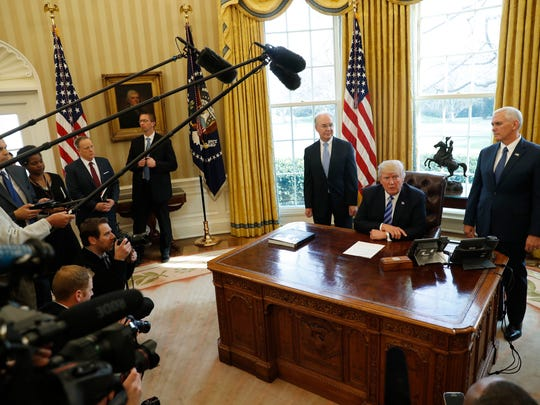 President Donald Trump, flanked by Health and Human Services Secretary Tom Price (left) and Vice President Mike Pence, meets with members of the media regarding the health care overhaul bill on March 24, 2017, in the Oval Office of the White House in Washington.