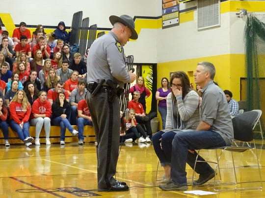 Lt. Scott Rike of the Ohio Highway Patrol reenacts for high school students Wednesday what it's like for parents to learn that their teenager has just died in a car wreck after they drive distracted.
