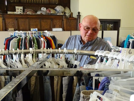 Pastor Mike Corwin of the Bucyrus Methodist Church looks through a rack of clothes available for the needy at the church's administrative building on Hopley Avenue.