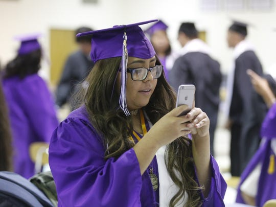 Ivie Herrera takes photos of friends inside the cafeteria at Kirtland Central High School on Thursday before the start of the graduation ceremony in Kirtland.