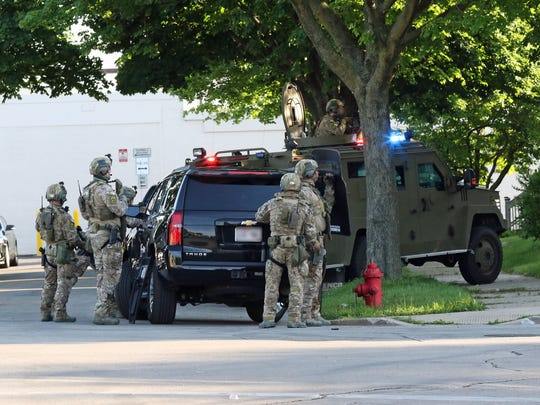 Federal and local law enforcement officers prepare to execute a search warrant in Milwaukee on Friday in connection with an investigation into the Gangster Disciples street gang.