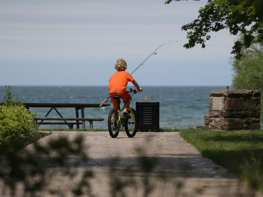 Azure Linder, 8, of Ohio bikes around Hamlin State Park with his grandfather, Chip Post, also of Ohio. Hamlin beach opens this weekend