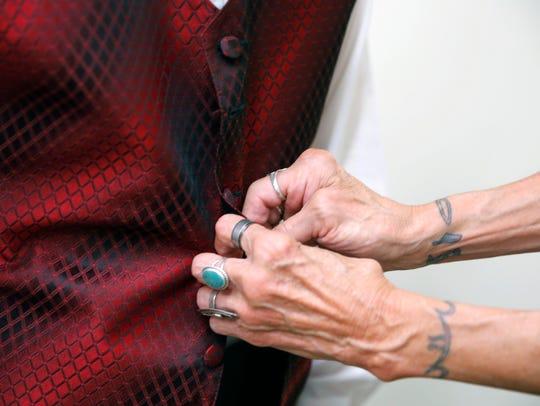 Gail Brouillard fastens a button for her grandson,