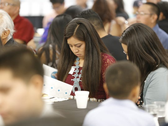 Navajo Preparatory School graduate Destinee D. Dale reviews a program during the Chief Manuelito Scholarship awards ceremony on Friday at the Henderson Fine Arts Center at San Juan College in Farmington.