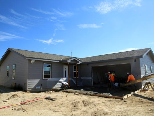 Employees of Hard Rock Builders pour the concrete for the driveway of an under-construction home on County Road 31190 on Friday.