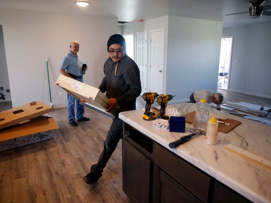 Khali Pioche, center, of Ultra Form Inc. places drawers back into the cabinet after installing the countertop of an under-construction home on County Road 31190 on Friday as Tres Rios Habitat for Humanity Treasure Frank Hayes, left, watches.