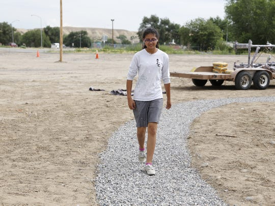 New Mexico Youth Conservation Corps member Isabella Tyler walks on the gravel trail the group developed at Nizhoni Park in Shiprock.