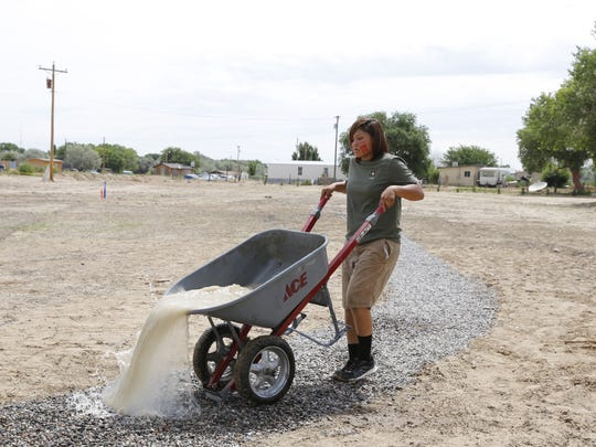 Laurael Eldridge spills water on the walking trail the group develop as part of renovation work at Nizhoni Park in Shiprock.