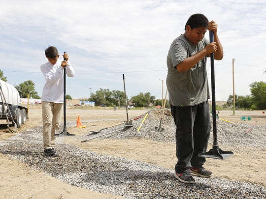 Richie Harvey, left, and Denzel Tsosie work on a gravel walking trail they helped develop as members of the New Mexico Youth Conservation Corps.