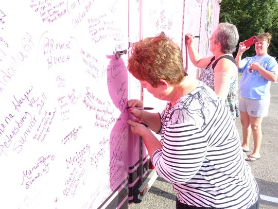 Cancer survivors sign their names on the Pink Heals