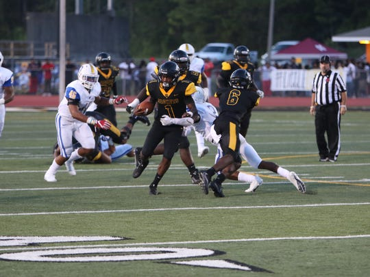 1. Starkville quarterback #1 Malik Brown breaks the tackle with help of #6 Rufus Harvey to gain a first down against Oxford High School.