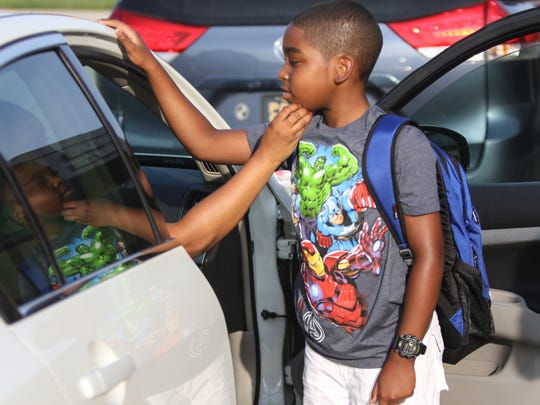 Fifth-grader and 10-year-old Harold Hall is embraced by his mother Jerrie while she was dropping him off on the first day of school at Pleasantville Elementary School.