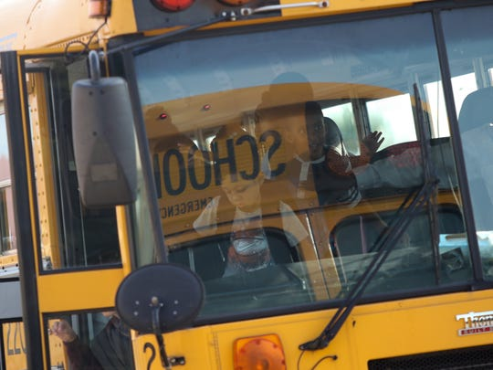 Children get off a school bus at Pleasantville Elementary School on the first day of school.