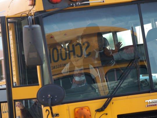 Children get off a school bus at Pleasantville Elementary