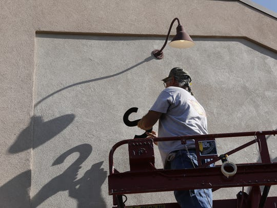 Sean Burke prepares to hang letters for a sign above