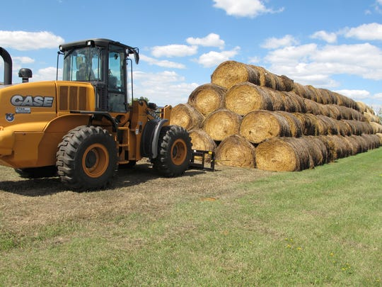 Bales of hay that have been donated for a lottery drawing to help drought-stricken farmers and ranchers are stacked at a site near the North Dakota State University campus in Fargo, N.D.