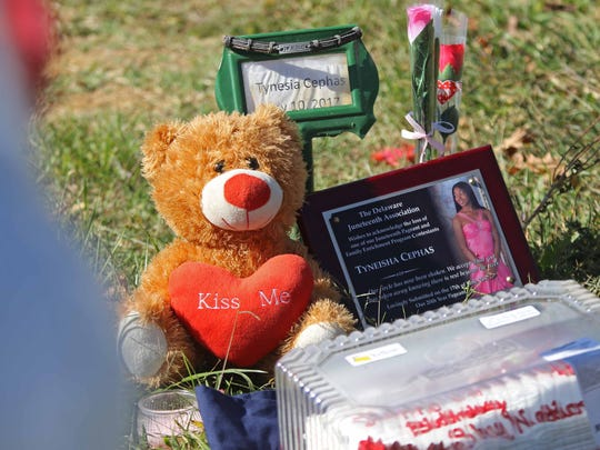 The grave of 16-year-old Tynesia Cephas is marked by her picture, flowers, a stuffed bear and birthday cake for her 17th birthday on Monday.