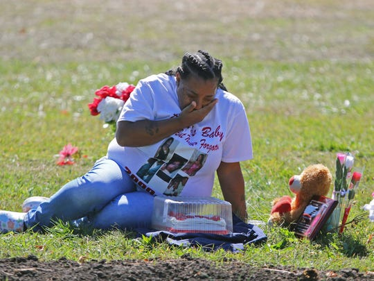 Na'Cole Nichols, aunt of 16-year-old Tynesia Cephas who was shot to death this past April, grieves by her graveside on what would have been her 17th birthday.