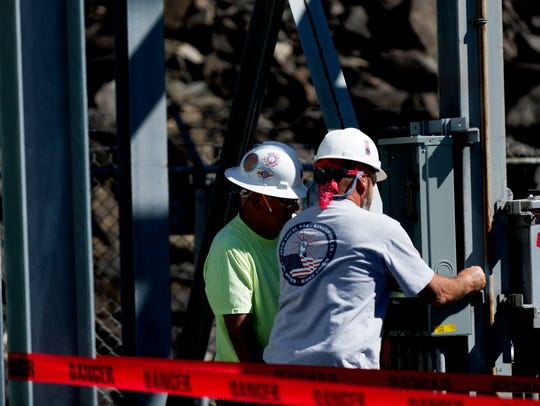 Workers install electrical equipment at South Holston