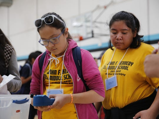 Ireland Gleason, a seventh-grader at John F. Kennedy Middle School in Gallup, tests orange juice for pH and conductivity during the STEM Exploration Day on Thursday at Navajo Preparatory School in Farmington.