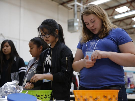 Tohatchi Middle School sixth-grader Kassandra Castaneda, left, and Kirtland Central High School sophomore Shelby Brown test the boats they constructed from aluminum foil during the penny boat challenge on Thursday at Navajo Preparatory School in Farmington.