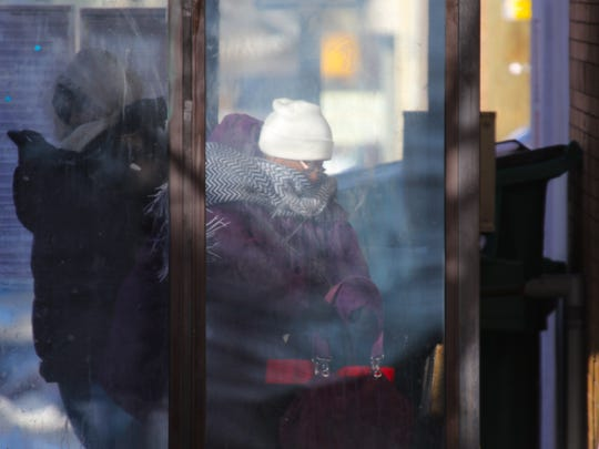 Commuters bundle up in a bus shelter while waiting on the next bus Friday morning on W. 6th St.