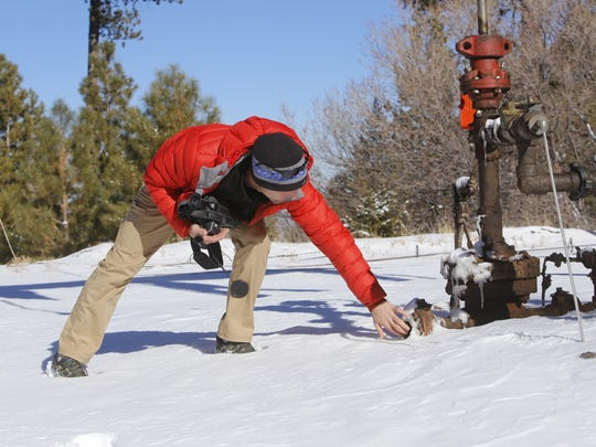 Pete Dronkers, southwest circuit rider for Earthworks, examines the end of a pipe at an oil well on Jan. 11 on Ch'ooshgai Mountain near Red Valley, Arizona.