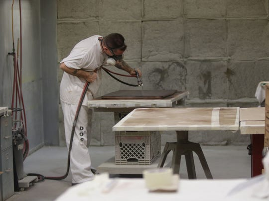 An inmate in the wood shop program refinishing a piece of furniture at James T. Vaughn Correctional Center.