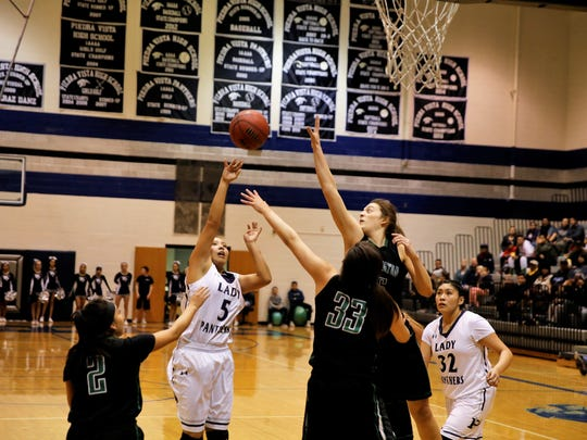 Piedra Vista's Alexis Long, No. 5 in white, knocks down a quick jumper in traffic during a non-district game on Monday, Jan. 8 against Farmington. PV will host Highland to open the 6A playoffs, while FHS opens the 5A playoffs at Kirtland Central.